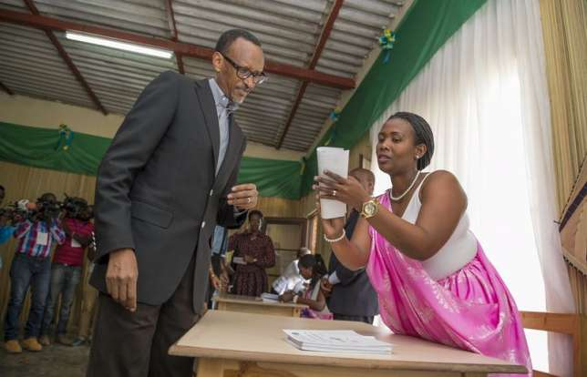 Rwanda President Paul Kagame is guided by polling assistants as he votes in Rwanda's capital Kigali