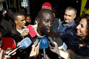 In this Tuesday, Dec. 22, 2015 picture, a Senegalese man named Ngame, who told reporters that he was rescued by Spain's coast guard traveling from Africa's western coast toward Spain's Canary Islands, speaks after discovering he won euro400,000 ($438,000) in Roquetas de Mar, in Almeria province, Spain. About 35 African migrants, including at least one rescued at sea from an overcrowded wooden boat, are among the top prize winners of Spain's Christmas lottery, according to the owner of the lottery agency that sold more than 1,000 tickets worth 400,000 euros ($438,000) each. (AP Photo/Javier Alonso)