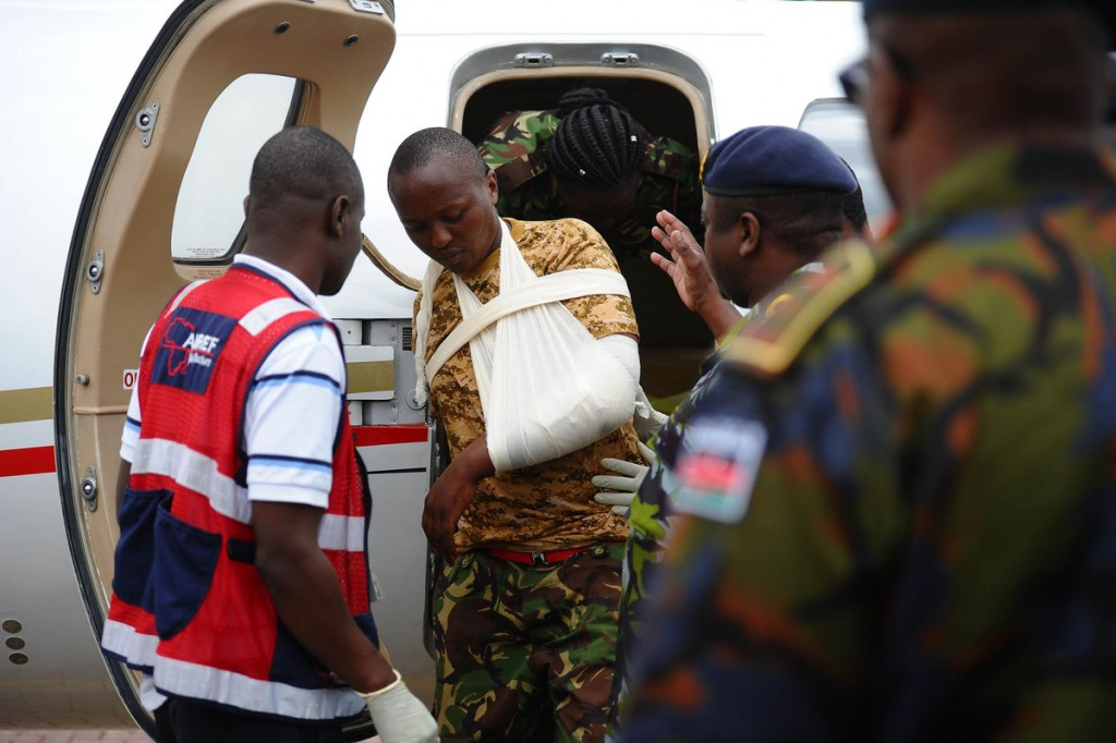 An injured Kenya Defence Force soldiers is helped steps out a plane prior to be transfered to a hospital after arriving in Nairobi following an attack by the Al-Qaeda-linked militants last week that killed over 100 Kenyan soldiers in a January 15 attack on an African Union base. Photographer: John Muchucha/AFP/Getty Images