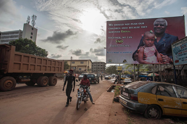 ASSOCIATED PRESS Two men pass an Ebola campaign poster in Freetown, Sierra Leone, on Jan. 15, 2016. A corpse has tested positive for Ebola in Sierra Leone, an official said Friday, the day after the World Health Organization declared the outbreak over in West Africa.