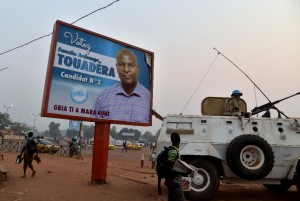 A UN peacekeeper sits on an armoured vehicle beside a campaign poster of presidential candidate Faustin Archange Touadera in Bangui on February 10, 2016 (AFP Photo/Issouf Sanogo)
