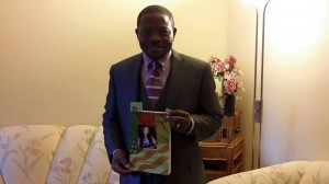 Oliver Asaah with a copy of the Broken Bond.Copies of the book will be on sale at the album launch