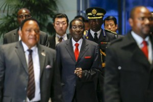 Zimbabwean President Robert Mugabe (C), pictured arriving for talks with Japanese Prime Minister Shinzo Abe in Tokyo on March 28, says he is still popular in his home country. KIMIMASA MAYAMA/AFP/GETTY IMAGES