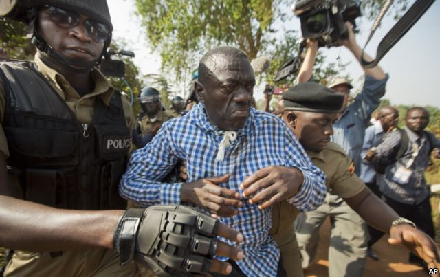Uganda's main opposition leader Kizza Besigye, center, is arrested by police and thrown into the back of a blacked-out police van which whisked him away and was later seen at a rural police station, outside his home in Kasangati, Uganda, Feb. 22, 2016.