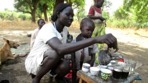 A woman makes coffee outdoors in South Sudan. A new partnership aims to build on the progress of revitalizing the country's fledgeling coffee industry. Photo by: Amy the Nurse / CC BY-NC-ND