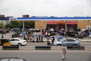 People queue to buy fuel at a station in Lagos, Nigeria, April 5. Attacks on oil pipelines and facilities have led to fuel shortages and power outages across Nigeria. AKINTUNDE AKINLEYE/REUTERS