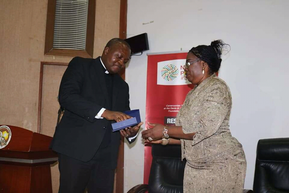 Foretia Foundation's COO Fri Asanga hands the Nelson Mandela Memorial award to Cardinal Tumi, represented by Father Michael Tchoumbou
