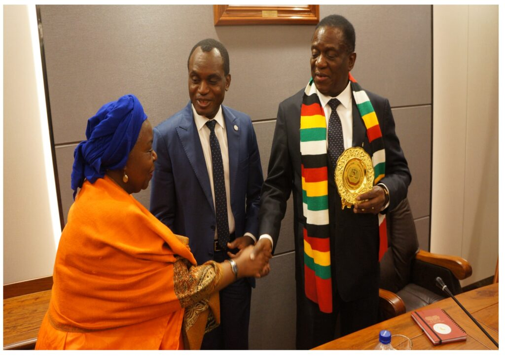 Zimbabwe's President Mnangawa greets a Judge of the Court Justice Hon Justice Tujilane Rose Chizumila after receiving a plaque from the Court's President Hon Justice Sylvain Oré (m).