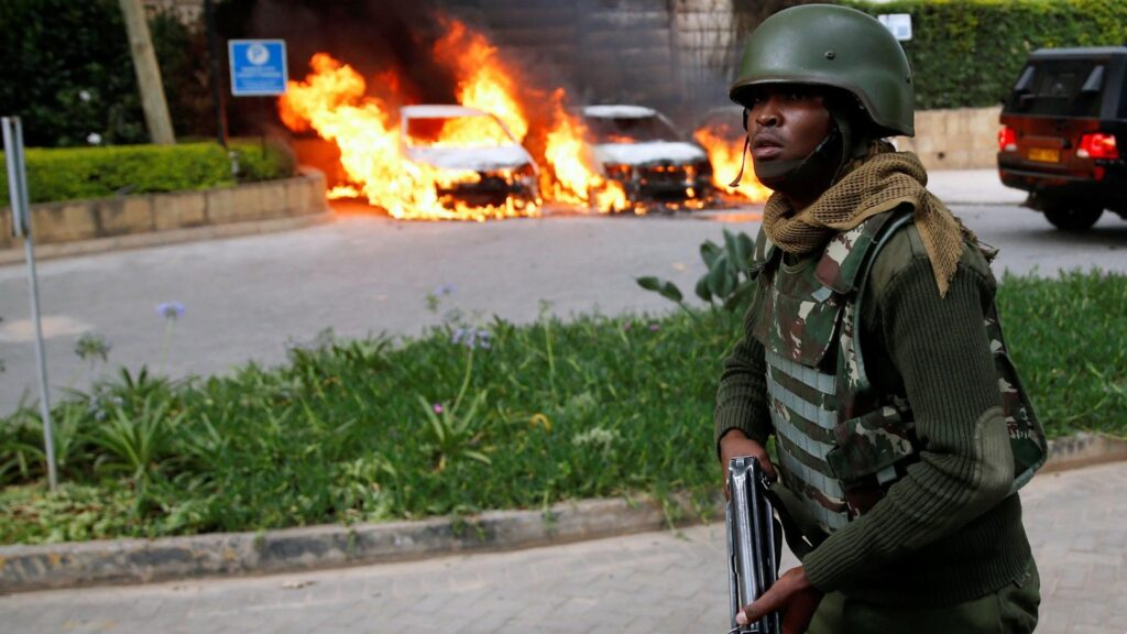A policeman runs past burning cars at the scene where explosions and gunshots were heard at the Dusit hotel compound, in Nairobi, Kenya Jan. 15, 2019.