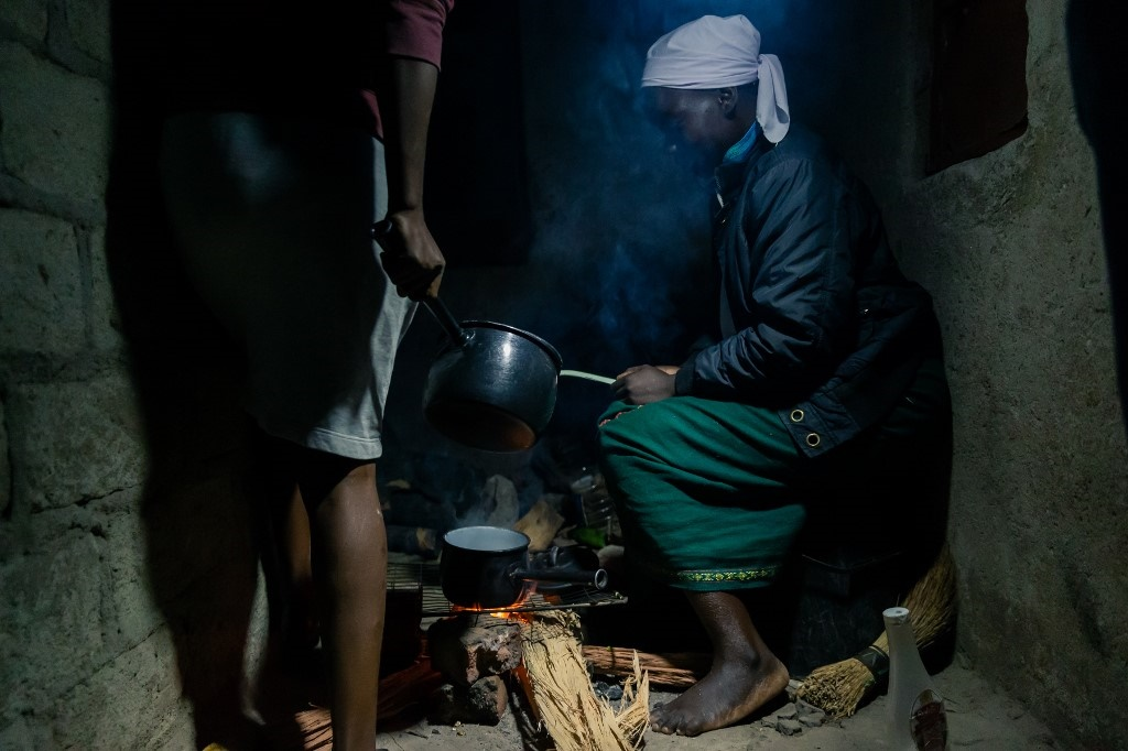Egenia Chishapira sits close by an open fire lit with a torch light as she uses firewood to prepare an evening meal for her family at her home in Mbare township, Harare. (Jekesai Njikizana/AFP)