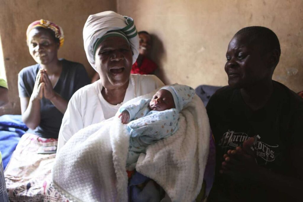 Esther Zinyoro Gwena holds one of the babies she has just delivered in her tiny apartment in the poor suburb of Mbare in Harare, Zimbabwe, Saturday, Nov. 16, 2019.Photo: Tsvangirayi Mukwazhi, AP