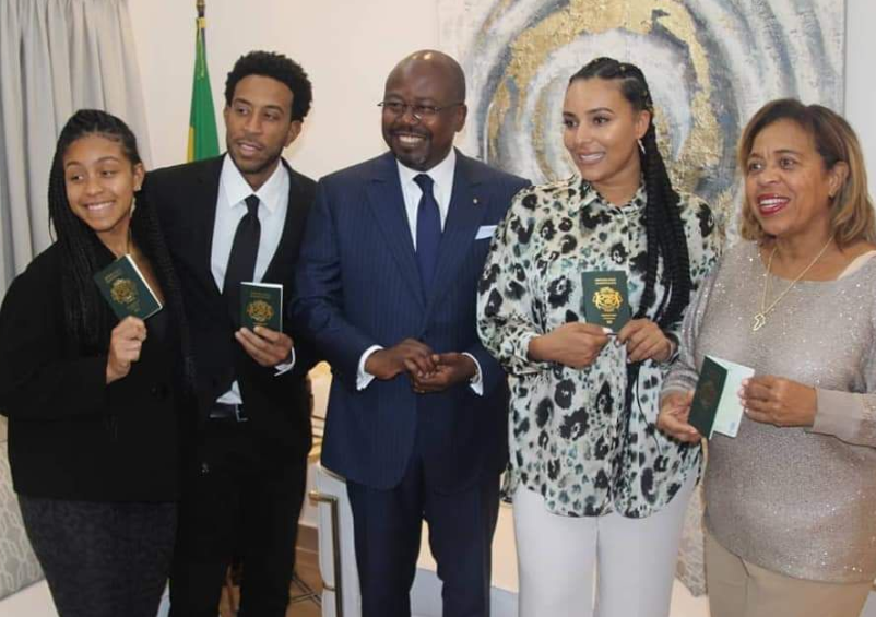Ludacris and family pose with Gabonese official brandishing their passports