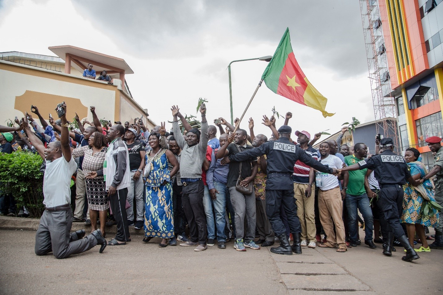 Hundreds of supporters raise their arms and wave the national flag while waiting to greet the Cameroonian opposition leader Maurice Kamto in Yaoundé on Oct. 5, the day of his release from prison. STRINGER/AFP via Getty Images