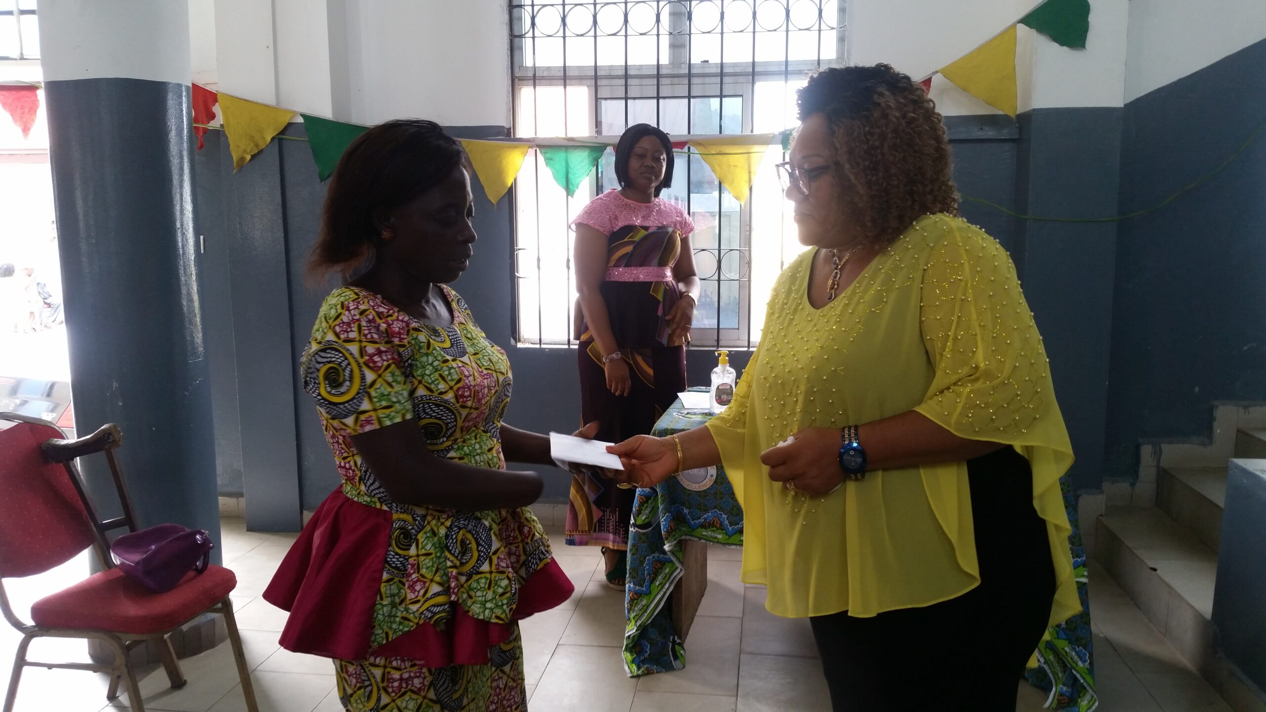1st Deputy Mayor of Buea Akawoh Minerva epse Molinge hands a cheque to a Displaced person residing in Buea