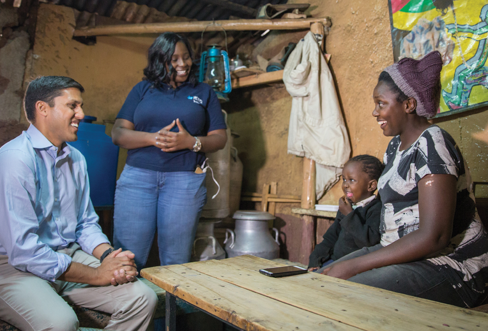 Dr. Rajiv J. Shah meets with a mother and her daughter to talk about The Rockefeller Foundation's work to bring electricity and lighting to the Kibera area in Kenya. | Photograph by Chad Holder