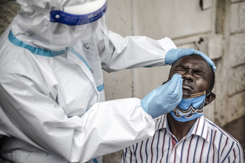 A Kenyan health worker uses a nasal swab to test a man for COVID-19 in the Kawangware slums of the capital, Nairobi.(Luis Tato / AFP/Getty Images)
