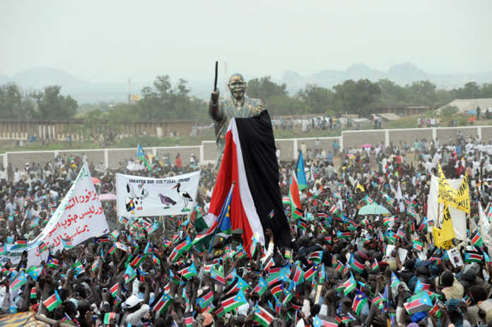 Enthusiastic South Sudanese surrounding the statue of its historic leader John country Garang. The promise of independence has not lived up to expectations