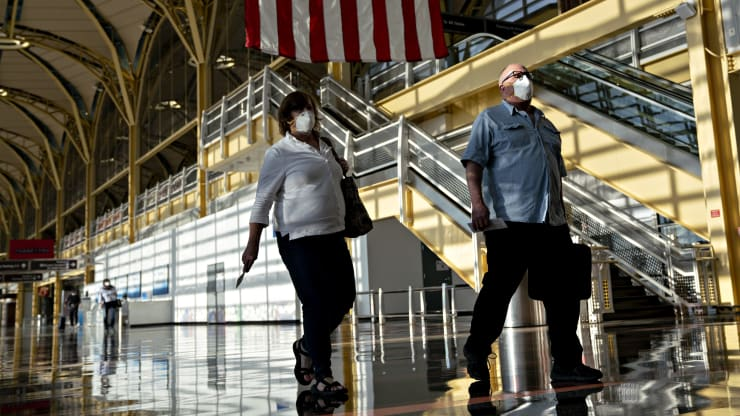 Travelers wearing protective masks walk through Ronald Reagan National Airport (DCA) in Arlington, Virginia, U.S., on Tuesday, June 9, 2020. Andrew Harrer | Bloomberg | Getty Images