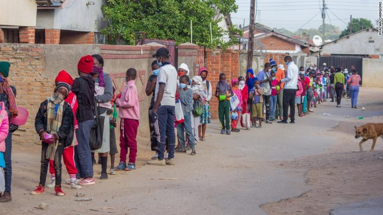 Children queue for food outside the kitchen of Murozoki in Zimbabwe.Photo CNN