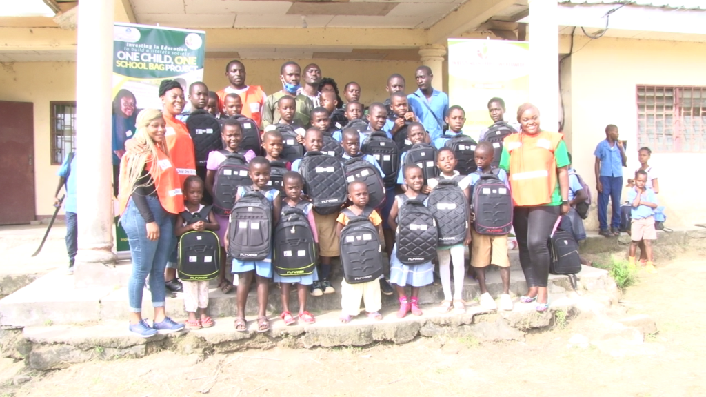 Beneficiaries of the One Child, One School Bag Project pose with school officials and members of IPW