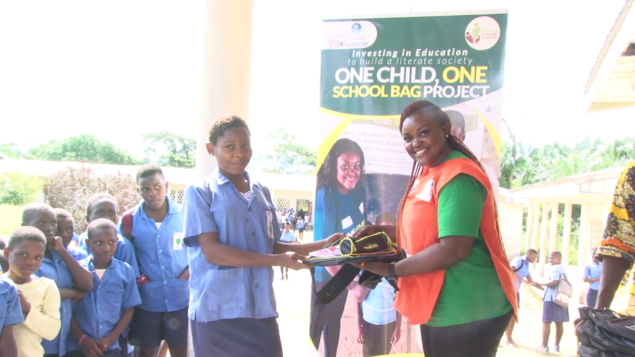 Ruth Besong, Executive Director of IPW hands school material to a Child at the Government Secondary School Mudeka