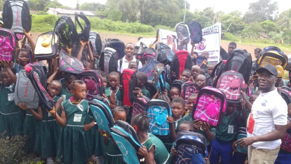 School children in the Moyamba district, Southern Sierra Leone pose with bags and books donated recently by the Senesie Foundation