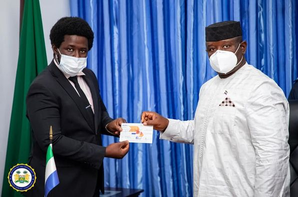 Presenting a check to President Bio. Under the eadership of Kaifala, the ACC has recovered millions of dollars in looted funds.