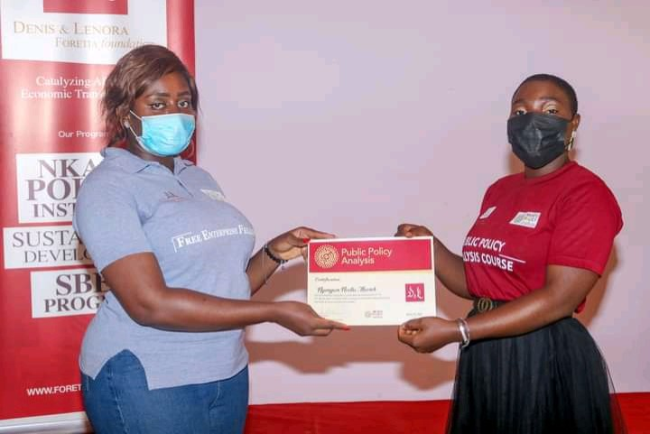 Ancel Langwa, Communication Manager at the Denis and Lenora Foretia Foundation hands certificate to a participant
