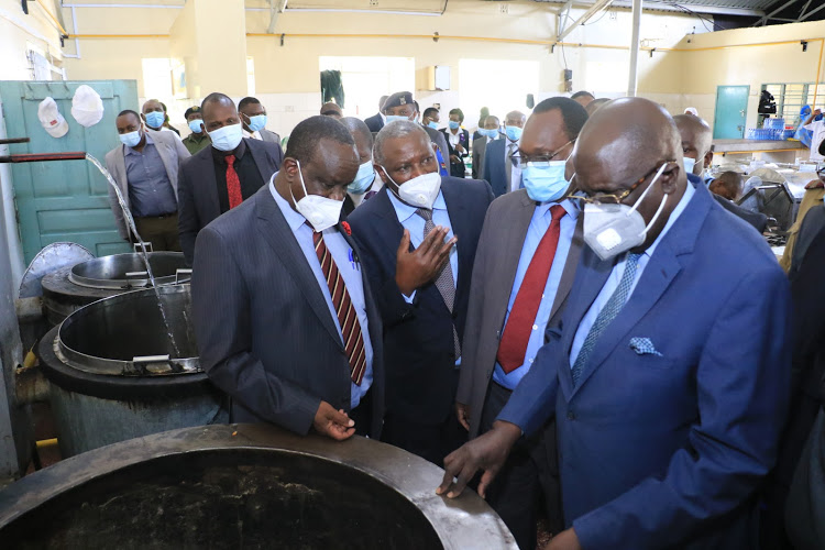 Education CS George Magoha (right), Environment PS Dr Chris Kiptoo (2nd right) and Equity Group MD and CEO Dr James Mwangi (3rd right) are taken through the kitchen fitted with modern cooking technology by Alliance High School Principal William Mwangi. Image: EQUITY BANK