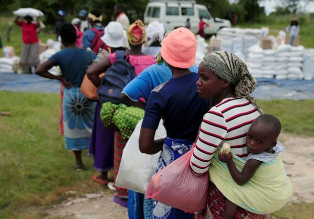 FILE PHOTO: Villagers queue to collect food aid distributed by the World Food Program (WFP) following a prolonged drought in rural Mudzi district, Zimbabwe, February 20, 2020. REUTERS/Philimon Bulawayo