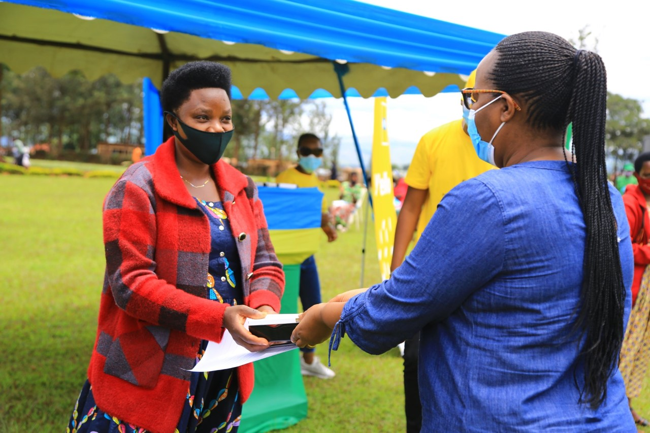 Minister for agriculture Dr. Gerardine Mukeshimana hands a smart phone to one of rural women during the event on Tuesday.